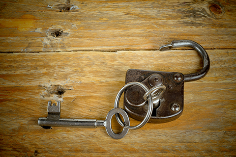 An open padlock with a key inside on a wooden background, representing the escape rooms at Escape Blue Ridge in Blue Ridge, Georgia. Guests staying at Xplorie participating properties can enjoy a free admission to the room of their choice.