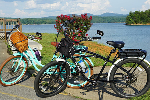 Two bicycles placed in front of a serene landscape seen while on the Pedego Bikes Fall Branch Falls Bike & Hike Tour in Blue Ridge, Georgia, which is available for free to guests staying at Xplorie participating properties.