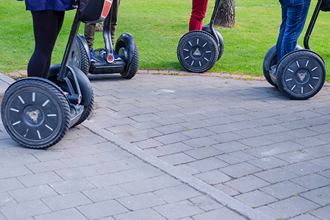 A group of people enjoys a Segway PT Downtown Blue Ridge Tour from Pedego Bikes in Blue Ridge, Georgia, which is available for free to guests staying at Xplorie participating properties.