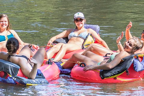 A group of women enjoy a tubing adventure from Rolling Thunder River Company in McCaysville, Georgia, which is available for free to guests staying at Xplorie participating properties.