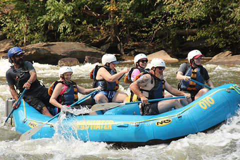 A group of people enjoying a thrilling whitewater rafting adventure with Wildwater in Copperhill, Tennessee, where guests staying at Xplorie participating properties can enjoy a free Ocoee Rafting Adventure.